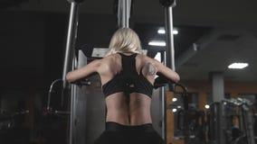 Feche acima da jovem mulher atlética que dá certo no equipamento do exercício da aptidão vídeos de arquivo