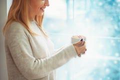 Feche acima da jovem mulher bonita na camiseta que guarda o copo do cacau ou do café quente com marshmallow ao estar a janela pró Fotos de Stock
