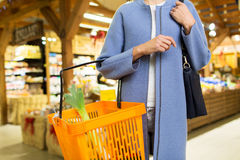 Feche acima da jovem mulher com a cesta do alimento no mercado Foto de Stock