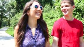 Feche acima da jovem mulher e do homem que rollerblading em um dia ensolarado no parque, guardando as mãos video estoque