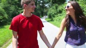 Feche acima da jovem mulher e do homem que rollerblading em um dia ensolarado no parque, guardando as mãos filme
