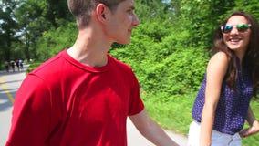 Feche acima da jovem mulher e do homem que rollerblading em um dia ensolarado no parque, guardando as mãos vídeos de arquivo