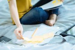 Feche acima da jovem senhora que toma notas amarelas Foto de Stock