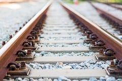 Feche acima da junção do trilho, âncora do trilho com linha da perspectiva das trilhas de estrada de ferro Imagens de Stock Royalty Free