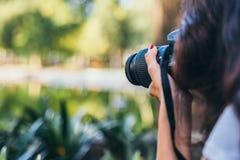 Feche acima da lente de um tiro do fotógrafo em um parque fotos de stock