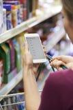 Feche acima da lista de compra da leitura da mulher do telefone celular imagens de stock