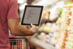 Feche acima da lista de compra da leitura do homem da tabuleta de Digitas no supermercado Foto de Stock Royalty Free