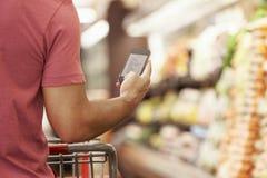 Feche acima da lista de compra da leitura do homem do telefone celular no supermercado fotografia de stock royalty free