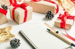 Feche acima da lista de presentes para o Natal Elaborando uma lista de presentes presentes no fundo de madeira branco do vintage  Fotos de Stock