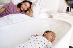 Feche acima da mãe adulta nova que encontra-se em sua cama que olha para baixo em seu bebê idoso de três meses que dorme em seu b imagens de stock royalty free