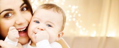 Feche acima da mãe com o bebê sobre luzes de Natal foto de stock