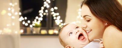 Feche acima da mãe com o bebê sobre luzes de Natal imagens de stock royalty free
