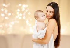 Feche acima da mãe com o bebê sobre luzes de Natal fotografia de stock