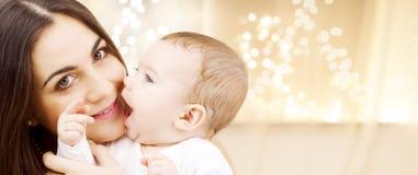 Feche acima da mãe com o bebê sobre luzes de Natal fotos de stock