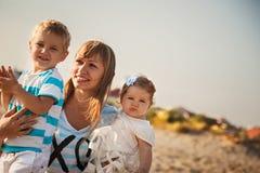 Feche acima da mãe de sorriso nova que abraça suas crianças pequenas, tendo o divertimento na praia junto, conceito de família fe imagem de stock