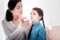 Feche acima da mãe nova que goteja suas filhas cheiram foto de stock