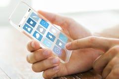 Feche acima da mão com ícones do menu no smartphone Fotos de Stock