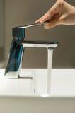 Feche acima da mão com torneira e volume de água Foto de Stock Royalty Free