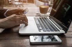 Feche acima da mão da mulher que mantém o cartão de crédito pago em linha e use o tom do vintage do portátil Imagem de Stock Royalty Free
