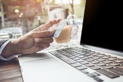 Feche acima da mão da mulher que mantém o cartão de crédito pago em linha e use o tom do vintage do portátil Imagens de Stock
