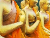 Feche acima da mão de estátuas douradas da monge no templo público Fotos de Stock Royalty Free