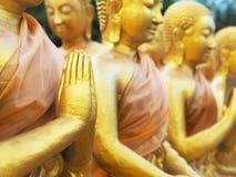 Feche acima da mão de estátuas douradas da monge no templo público Imagem de Stock