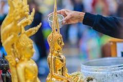 Feche acima da mão de povos tailandeses ao banhar o rito às imagens de buddha Imagem de Stock