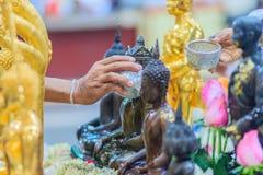 Feche acima da mão de povos tailandeses ao banhar o rito às imagens de buddha Imagem de Stock Royalty Free