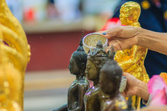 Feche acima da mão de povos tailandeses ao banhar o rito às imagens de buddha Fotografia de Stock