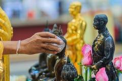 Feche acima da mão de povos tailandeses ao banhar o rito às imagens de buddha Fotos de Stock