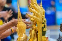 Feche acima da mão de povos tailandeses ao banhar o rito às imagens de buddha Imagens de Stock Royalty Free