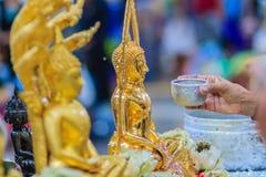 Feche acima da mão de povos tailandeses ao banhar o rito às imagens de buddha Imagens de Stock