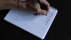 Feche acima da mão de um homem escreve uma equação matemática filme