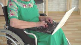 Feche acima da mão de uma mulher idosa que datilografa em um portátil e que senta-se em uma cadeira de rodas vídeos de arquivo
