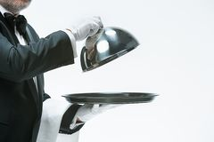 Feche acima da mão do garçom com tampa da tampa da campânula da bandeja e do metal imagem de stock royalty free