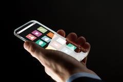 Feche acima da mão do homem de negócios com smartphone de vidro Fotografia de Stock