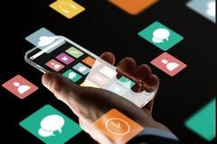 Feche acima da mão do homem de negócios com smartphone de vidro Imagens de Stock