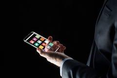 Feche acima da mão do homem de negócios com smartphone de vidro Fotografia de Stock Royalty Free