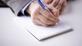 Feche acima da mão do homem de negócios que escreve ao bloco de notas filme