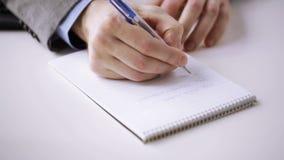Feche acima da mão do homem de negócios que escreve ao bloco de notas vídeos de arquivo