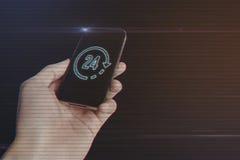 Feche acima da mão do homem que guarda o smartphone com 24 horas de ícone Fotos de Stock Royalty Free