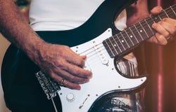 Feche acima da mão do homem que joga a guitarra na fase para o fundo imagem de stock royalty free