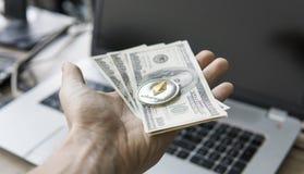 Feche acima da mão do homem que mantém a moeda de Ethereum connosco nota de dólar contra um portátil na parte traseira Ethereum é Fotos de Stock