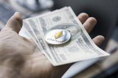 Feche acima da mão do homem que mantém a moeda de Ethereum connosco nota de dólar contra um portátil na parte traseira Ethereum é Imagens de Stock