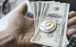 Feche acima da mão do homem que mantém a moeda de Ethereum connosco nota de dólar contra um portátil na parte traseira Ethereum é Foto de Stock Royalty Free