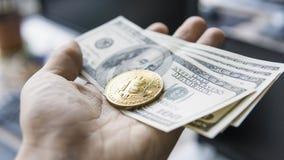Feche acima da mão do homem que mantém uma moeda dourada do bitcoin connosco nota de dólar contra um portátil na parte traseira B Foto de Stock