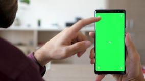 Feche acima da mão do homem que toca e que usa em um smartphone com zombaria verde do croma da tela acima nela video estoque