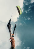 Feche acima da mão do kitesurfer da imagem com o papagaio no céu azul Fotografia de Stock