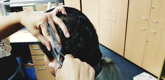 Feche acima da mão do ` s do barbeiro usando o pente e as tesouras que cortam o homem do cabelo foto de stock