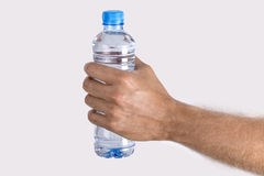 Feche acima da mão do ` s do homem que mantém a garrafa da água isolada em b branco Fotos de Stock Royalty Free